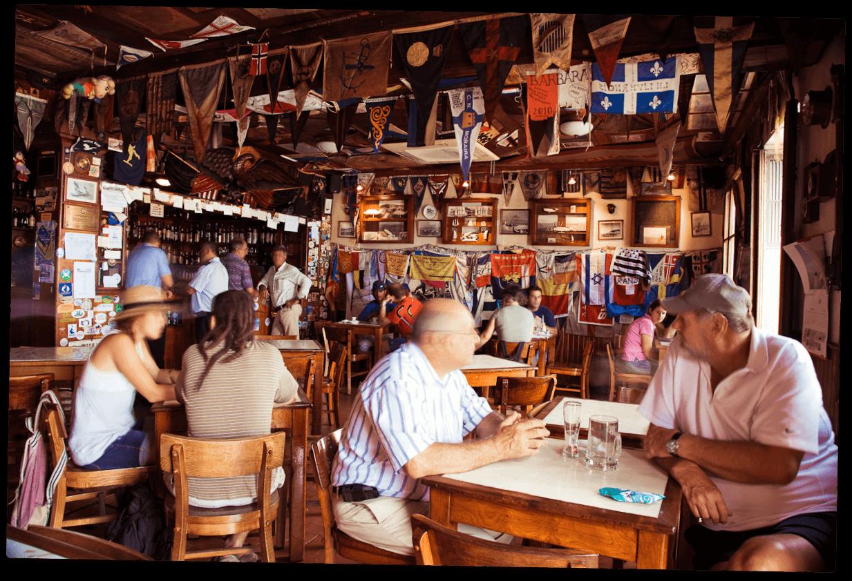 Fotografia antiga do interior do Peter Cafe Sport com o proprietário e alguns membros do navio H.M.S. Lusitania II da Royal Navy.