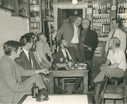 Old photograph of the interior of Peter Cafe Sport with the owner and some members of the ship H.M.S. Lusitania II of the Royal Navy.