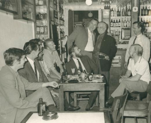Fotografia antiga do interior do Peter Cafe Sport com o proprietário e alguns membros do navio H.M.S. Lusitania II da Royal Navy