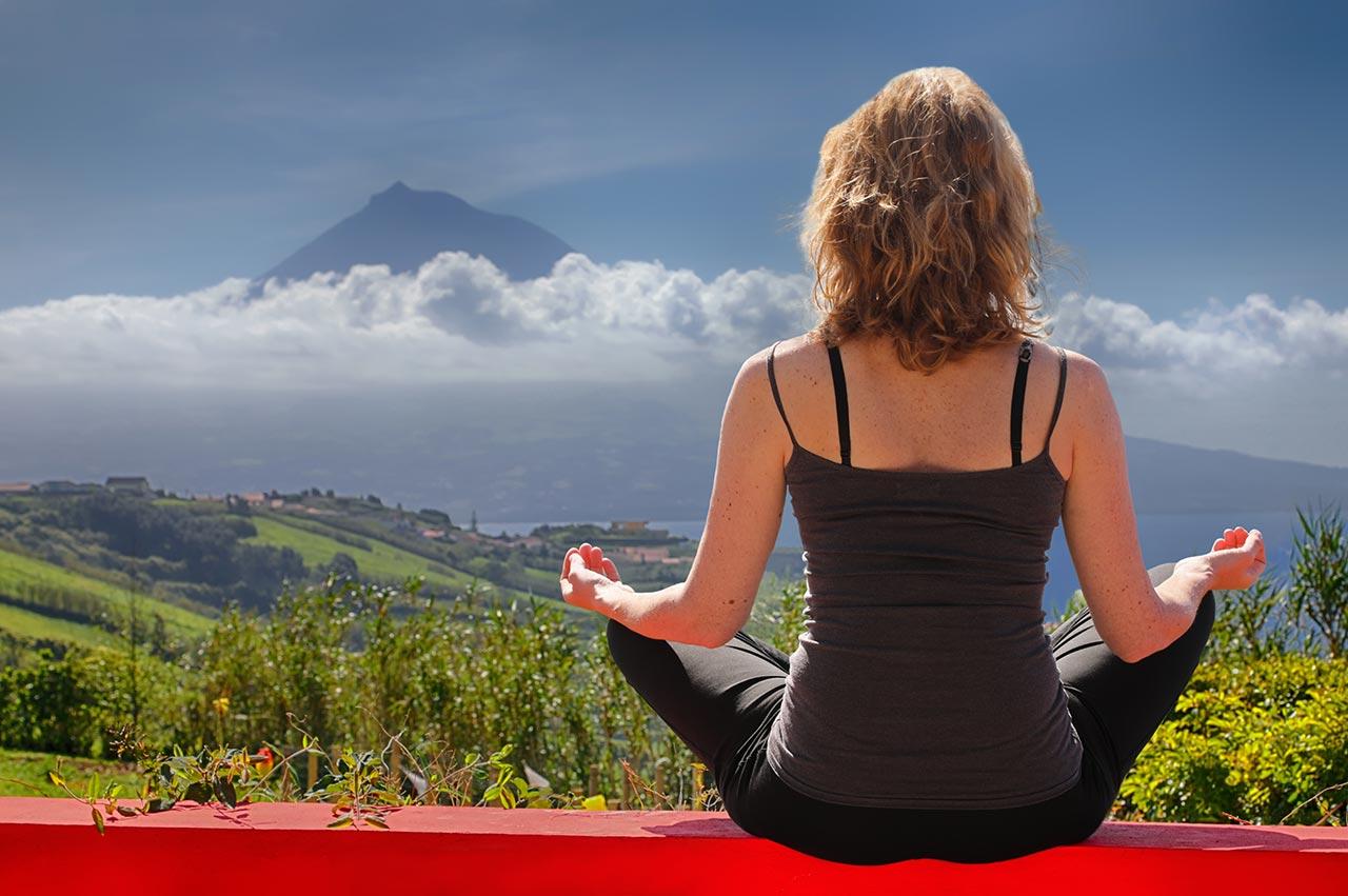 uma mulher meditando durante a atividade de renascimento do sol no Faial, com vista para a ilha do pico