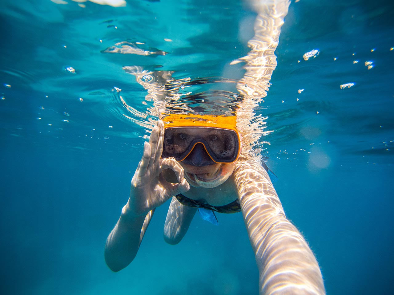 a girl snorkeling in the sea of Faial, in the Azores